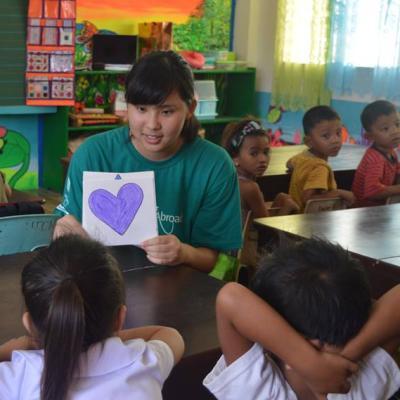 Een Japanse vrijwilliger werkt met kinderen en geeft les over vormen op het kinderopvang project in de Filippijnen.